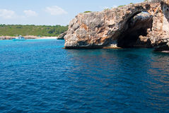 Natural arch and recreational boat at Cala Antena Royalty Free Stock Photography