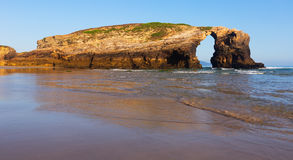 Natural arch at sand beach Stock Images