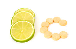 Natural or artificial c vitamin?. Some lime slices and a C letter from c vitamin tablets Stock Images