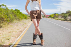 Natural attractive woman posing while hitchhiking. On a deserted road in summertime Royalty Free Stock Image