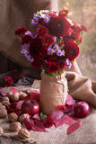 Natural autumn garden flower bouquet composition. Decor design in rustic vase  with apples nuts and red leaves on vintage wooden table background. Natural light Royalty Free Stock Images