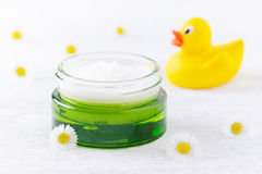Natural baby cosmetic, cream and chamomile flowers, a duck, selective focus. Natural baby cosmetic, cream and chamomile flowers, a duck toy, defocused stock photos