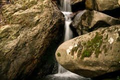 Natural background of beautiful soft river waterfall flowing hidden in forest rocks Royalty Free Stock Photos