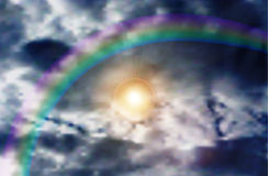 Natural background of blue sky, rainbow and scintillating sun through clouds Royalty Free Stock Photography