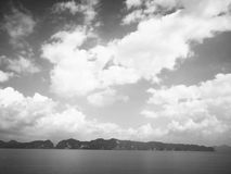 Natural background and hopeless waiting concept. The backdrop of. The foggy island, emerald sea water and the blue sky is full of clouds. Selective focus and Royalty Free Stock Images