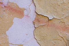 Natural wall with peeling paint. Natural background of old wall with shabby and peeling paint and plaster with cracks and stains of paint stock photo