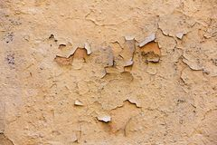 Natural wall with peeling paint.  cracks and stains of paint. Natural background of old wall with shabby and peeling paint and plaster with cracks and stains of royalty free stock photography
