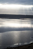Natural background. Shining through the clouds over the water Stock Image