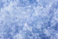 Natural background snowflake closeup. Natural snowflakes close-up on background of snow on sunny day Royalty Free Stock Photo