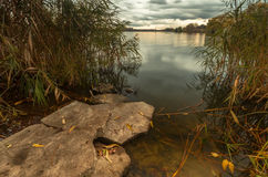 Natural background with stone, grass and water. Autumn landscape with lake and stone Royalty Free Stock Image