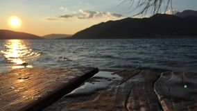 Natural background with sunset over sea and wooden boards. Sunny evening over small sea bay, background with water surface and old weathered boards of wooden stock video