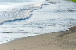 Natural background of waves rolling into the beach. Seascape background of gentle sea waves lapping along the coastline of Black Sea, Bulgaria Stock Images