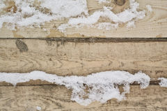 Natural background winter texture. Pine boards in the snow, in the forest Stock Image