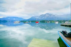 Natural and beautiful alpine Lake Mondsee. Morred boats float lazily on calm natural and beautiful alpine Lake Mondsee surrounded by Austrian Alps royalty free stock photography