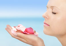 Natural beauty. Female holding (silk) rose petals up to her nose Stock Image
