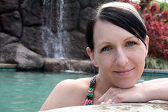 Natural Beauty. Young woman smiles at pools edge, waterfall in the background Stock Images