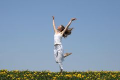 Natural beauty. Young woman in summer white clothes dancing in a flowering field Royalty Free Stock Images