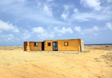 Off-road Aruba. Amazing sand desert landscape with some building on blue sky and white clouds background. Royalty Free Stock Images