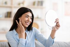 Free Natural Beauty. Asian Girl Holding Magnifying Mirror And Touching Her Perfect Skin Royalty Free Stock Images - 193705139