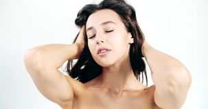 Natural Beauty Athletic Lady. Young athletic brunette lady playing with hair and looking to camera isolated on white background, natural beauty stock video footage