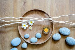 Natural beauty, ayurveda spa or wellness with wood and pebbles. Natural beauty, ayurveda spa or detox wellness with beautiful pebbles, candle, fresh flowers and royalty free stock photography
