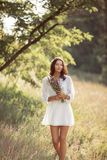 Natural beauty girl with bouquet of flowers outdoor in freedom enjoyment concept. Beautiful young woman in white dress collecting wild flowers at the rural royalty free stock photography
