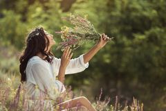 Natural beauty girl with bouquet of flowers outdoor in freedom enjoyment concept. Beautiful young woman in white dress smelling wild flowers at the rural sunny royalty free stock photo