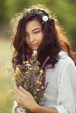 Natural beauty girl with bouquet of flowers outdoor in freedom enjoyment concept. Portrait photo. Beautiful young woman in white dress holding wild flowers at royalty free stock image