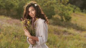 Natural beauty girl with bouquet of flowers outdoor in freedom enjoyment concept. Portrait photo. Beautiful young woman in white dress holding wild flowers at stock video footage