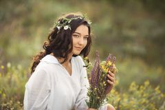 Natural beauty girl with bouquet of flowers outdoor in freedom enjoyment concept. Portrait photo. Beautiful young woman in white dress collecting wild flowers at stock image