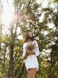 Natural beauty girl in medow outdoor in freedom enjoyment concept. Beautiful young woman in white dress collecting wild flowers at the rural sunny landscape stock photo