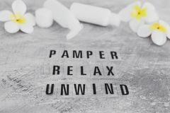 Free Natural Beauty Products, Lotions And Essential Oil Bottles Surrounded By Flowers And Shells With Pamper Relax Unwind Text Royalty Free Stock Photography - 164501967