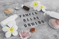 Free Natural Beauty Products, Lotions And Essential Oil Bottles Surrounded By Flowers And Shells With Pamper Relax Unwind Text Royalty Free Stock Photography - 164502097