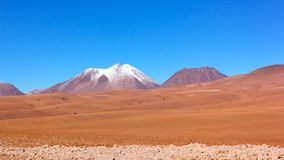 Natural beauty of unspoiled desert landscape, Chile. Colorful landscape of rocks, sandy valleys, and volcanic mountains with snow peaks in Atacama Desert, Chile royalty free stock photos