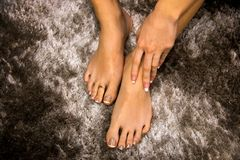 Well cared woman feet from top with french manicure lacquer on toes, hand touching skin, above view abstract background royalty free stock photo