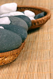 Natural bebbles on the rattan background. Natural pebbles on the rattan background. Suitable for spa and relaxation setting Royalty Free Stock Photos