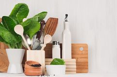 Natural beige and brown wooden kitchenware and green plant on light white wood background, copy space. Natural beige and brown wooden kitchenware and green Stock Photography