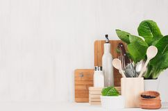 Natural beige and brown wooden kitchenware and green plant on light white wood background, copy space. Natural beige and brown wooden kitchenware and green Royalty Free Stock Photos