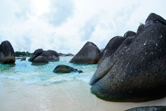 Natural black rock formation on the seashore at the beach in Belitung Island. Natural black rock formation on the seashore at the beach in Belitung Island at Stock Photos