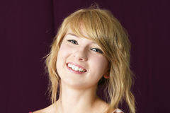 Natural blond girl smiling. Portrait of a natural, young beautiful blond girl smiling royalty free stock photos