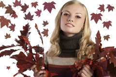 Natural blonde beauty holding some autumn leaves. Blonde natural girl holding red autumn leaves in her hand on white Royalty Free Stock Photo