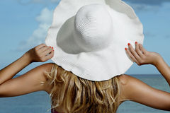 Natural blonde girl smiling wearing an hat on the beach Stock Photos