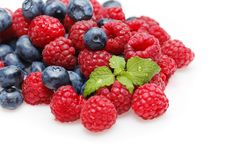 Blueberry and raspberry berries isolated on white background. Natural blueberry and raspberry berries with mint leaves isolated on white background. copy space Stock Image