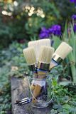The Feminine Painting Project. Natural boar hair bristle paint brushes of different shapes in a glass jar on a gray weathered wood step surrounded by purple Royalty Free Stock Photos