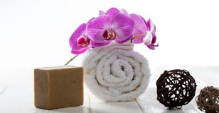 Olive oil soap, rolled towel and orchids for healthy purity. Natural body care and green softness concepts with sustainable olive oil soap, pure rolled up towel Stock Photos