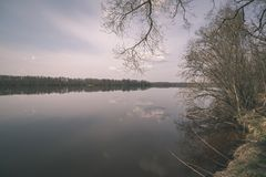Natural body of water. pond with reflections - vintage retro loo. Natural body of water. pond with reflections of trees and clouds in calm water surface stock images