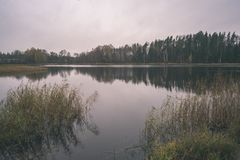 Natural body of water. pond with reflections - vintage retro loo. Natural body of water. pond with reflections of trees and clouds in calm water surface royalty free stock image