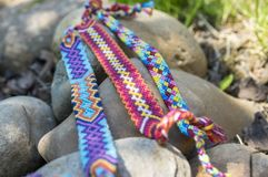 Three hadmade color bracelets of friendship on the stones royalty free stock image
