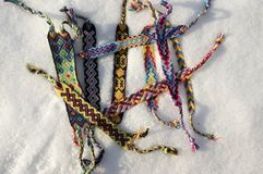Natural bracelets of friendship in a row, colorful woven friendship bracelets, snow background, rainbow colors, checkered pattern. Natural bracelets of stock photography