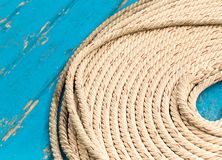 Natural braided rope stacked in a circle row of parallel ropes on a blue deck boat background royalty free stock image